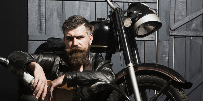 Thoughtful unshaven male biker in leather jacket sitting near motorcycle in garage with big bone skull antlers of stuffed animal looking forward on wooden wall background, horizontal picture